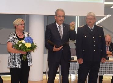 Landrat Harald Altekrüger (Mitte) präsentiert das neue Ärmelabzeichen, das Wolfhard Kätzmer ab Ende Juli tragen wird. Kreistagspräsidentin Monika Schulz-Höpfner (links) gratuliert ebenfalls.