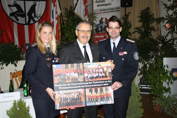 Anja Aldermann und Robert Buder überreichen Landrat Harald Altekrüger (Mitte) eine Collage der Feuerwehr-WM. Als Dank für die Unterstützung der Finanzierung.