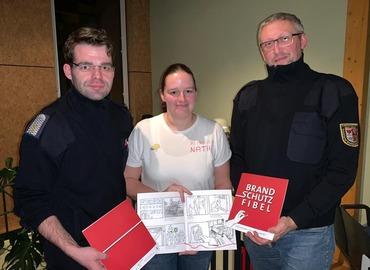 Robert Buder (Vorsitzender KFV), Nathalie Scherer (Brandenburgs beliebteste Brandschutzerzieherin) und Stefan Kothe (amt. Kreisjugendfeuerwehrwart) präsentieren die dt-polnischen Brandschutzfibeln