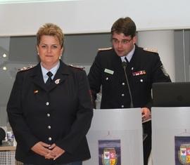 Robert Buder (Hintergrund) verliest die Urkunde zu Auszeichnung der ehemaligen Schatzmeisterin der Kreisjugendfeuerwehr Spree-Neiße