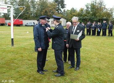 Kreisjugendfeuerwehrwart Christian Rösiger übergibt Bernd Schulze das Ehrenzeichen der Landesjugendfeuerwehr Brandenburg in Bronze aus.