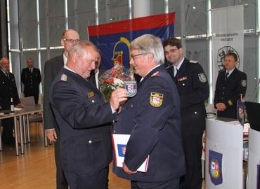 Werner-Siegwart Schippel übergibt das neue Ärmelabzeichen und gratuliert dem Kreisbrandmeister Wolfhard Kätzmer zu seiner Ehrenmitgliedschaft im Kreisfeuerwehrverband Spree-Neiße e.V.