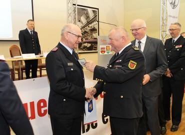 Der Präsident des Landesfeuerwehrverbandes, Werner-Siegwart Schippel, überreicht Siegmund Rückmann das Ärmelabzeichen als Ehrenmitglied