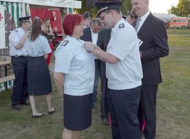 Kameradin Katrin Kraljic bekommt vom Vorsitzenden des Kreisfeuerwehrverbandes die Auszeichnung angesteckt.