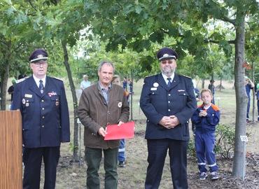 Der Ehrenlandesbrandmeister Jürgen Helmdach und der Stellvertretende Vorsitzende des KFV SPN e.V. Jörg Fischer überreichen die Auszeichnungsurkunde